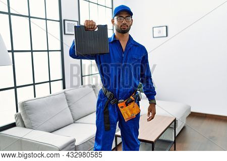 Young indian technician holding toolbox and screwdriver at house thinking attitude and sober expression looking self confident