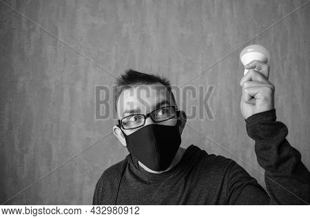 Caucasian Man In Protective Mask With Bulb In His Hand On Gray Background With Copy Space. Monochrom