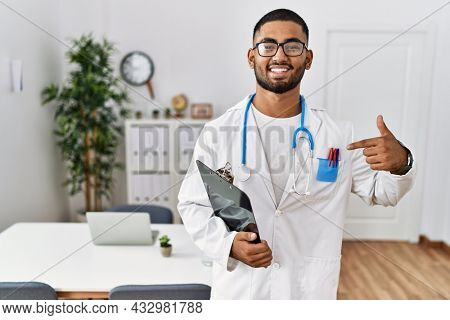 Young indian man wearing doctor uniform and stethoscope looking confident with smile on face, pointing oneself with fingers proud and happy.