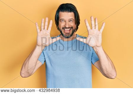 Middle age caucasian man wearing casual clothes showing and pointing up with fingers number ten while smiling confident and happy.