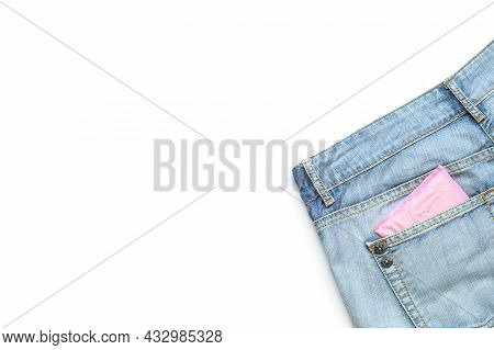 Menstruation Sanitary Pad In Pink Packaging In Back Pocket Of Light Blue Jeans On White Background.f
