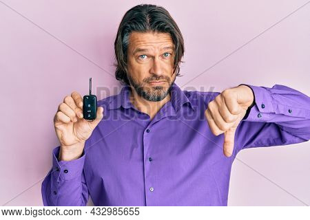 Middle age handsome man holding key of new car with angry face, negative sign showing dislike with thumbs down, rejection concept