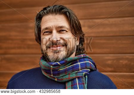 Middle age handsome man smiling leaning on the wall