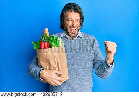 Middle age handsome man holding paper bag with groceries screaming proud, celebrating victory and success very excited with raised arms