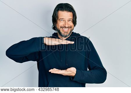 Middle age caucasian man wearing casual sweatshirt gesturing with hands showing big and large size sign, measure symbol. smiling looking at the camera. measuring concept.