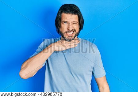 Middle age caucasian man wearing casual clothes cutting throat with hand as knife, threaten aggression with furious violence