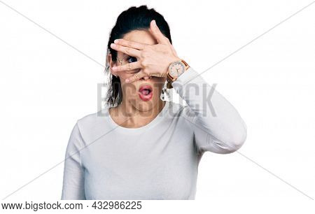 Young hispanic woman wearing casual clothes peeking in shock covering face and eyes with hand, looking through fingers with embarrassed expression.