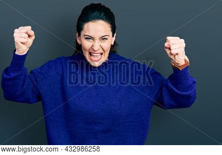 Young hispanic woman wearing casual clothes angry and mad raising fists frustrated and furious while shouting with anger. rage and aggressive concept.