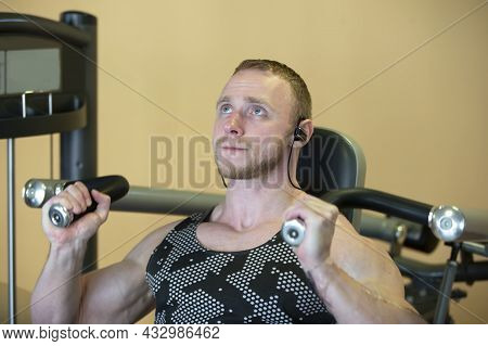 A Handsome Man Of An Athletic Physique Is Engaged On The Simulator.