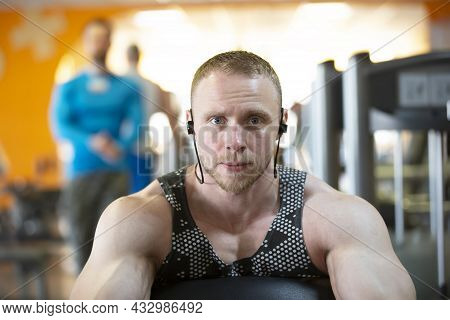 A Handsome Young Strong Man Of An Athletic Physique Is Engaged On A Sports Simulator.