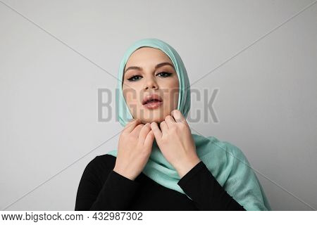 Young Arabian Woman Correcting Her Hijab, Isolated Over White Wall.