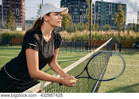 Tennis Player In Sun Cap Is Leaning On Net While Standing On Court Holding Tennis Racket And Ball, L
