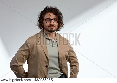 A Young Businessman In Eyewear Smiling Broadly Posing Indoors. Male Entrepreneur Resting In The City
