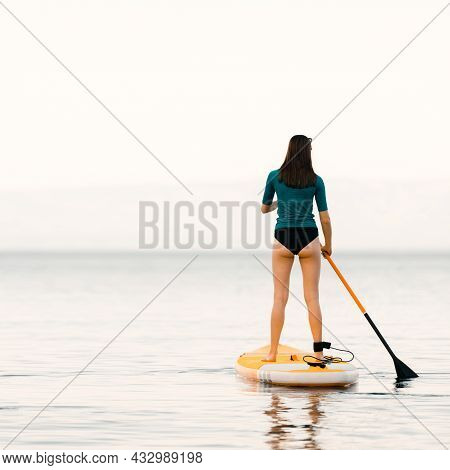 Young Girl On A Sup Board With A Paddle In Her Hand - Shot From The Back, Calm Surface Of The Sea, C