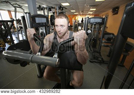 A Young Man Of Athletic Physique Is Engaged In The Gym.