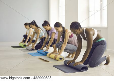 Group Of Women Rolling Up Rubber Mats After Fitness Workout Or Yoga Class At Gym