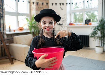 Happy girl in black attire asking for halloween treats in front of camera