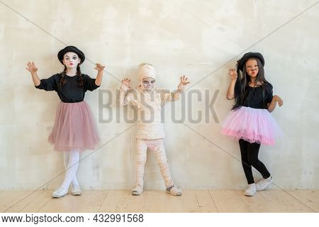 Three little kids in halloween attire standing along white wall in front of camera