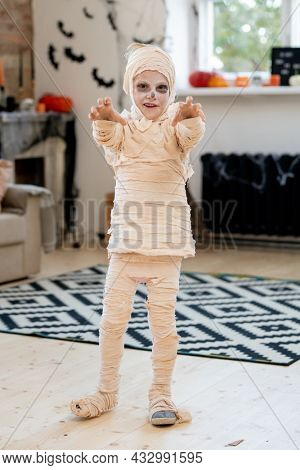 Cute boy wrapped into bandage frightening you while standing in front of camera