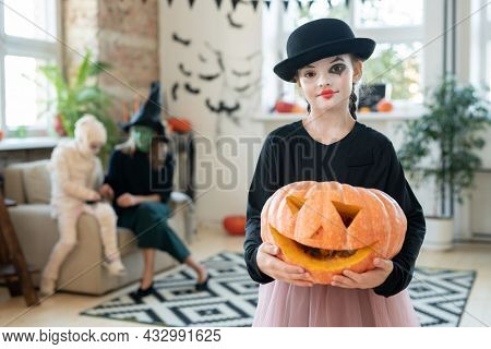 Happy halloween girl in black attire holding jack-o-lantern while standing in living-room