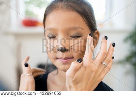 Little girl keeping eyes closed while woman applying dark grey eyeshadow on her eyelids for halloween