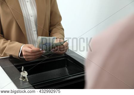 Cashier With Money At Currency Department Window In Bank, Closeup
