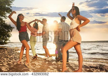 Group Of Friends Having Fun Near River At Summer Party