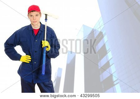 Young male window cleaner with wiper over building with glass facade poster
