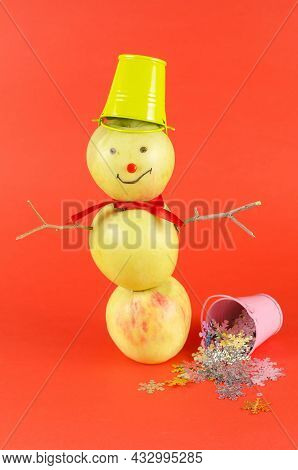Apple Snowman With A Green Bucket On His Head Standing On A Red Background. Creative Snowman Of Thre