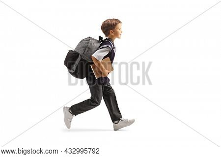 Full length profile shot of a schoolboy in a uniform running and holding a book isolated on white background