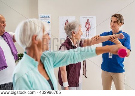 Group of old people using dumbbells for workout session with physiotherapist. Group of active seniors exercising in clinic with trainer. Elderly woman lifting weight for wellness with trainer.