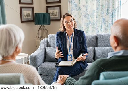 Social worker, talking to old man and woman for insurance plans on retirement. Happy supporter with senior people during a home consultation: counseling and psychological session at home.