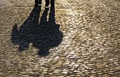 Silhouette and shadows of people walking on brick pavement poster