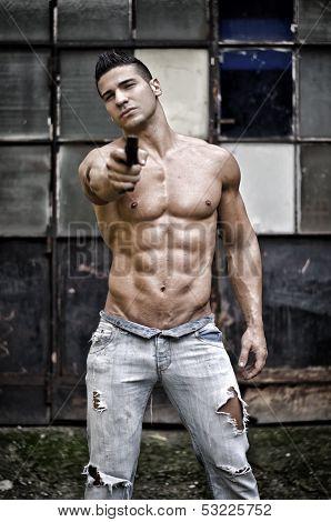 Menacing muscular young man shirtless pointing handgun to camera outdoors poster