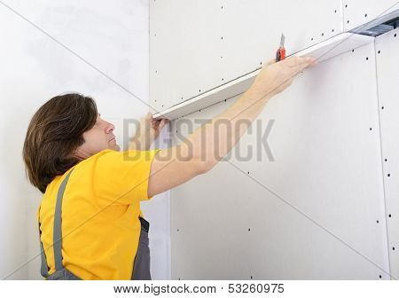 Man working with plasterboard, try on drywall panel to wall