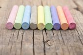 colorful chalks on old wooden table poster