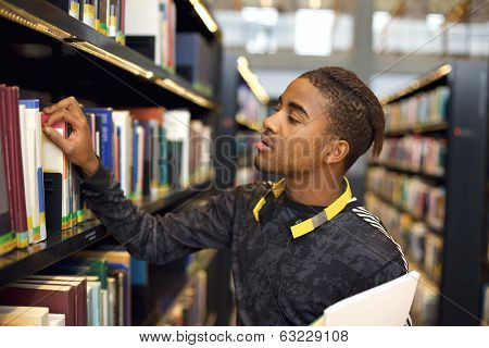 Young Man Looking For Books At Public Library