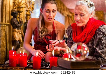 Female Fortuneteller or esoteric Oracle, sees in the future by hand reading during a Seance to interpret them and to answer questions