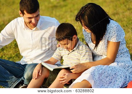 Cheerful family on beautiful summer meadow enjoying learning from the book