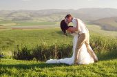 Bride and groom outside garden wedding with African Natal Midlands mountain scenery background poster