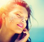 Suntan Lotion Woman Applying Sunscreen Solar Cream. Beautiful happy cute Girl applying Sun Tan Cream on her Face over ocean background. Sun Tanning. Skin care and Protection. Vacation poster