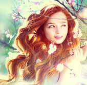 Spring beauty girl with long red blowing hair outdoors. Blooming trees. Romantic young woman portrait. Nature poster