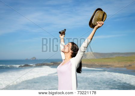 Blissful Woman Raising Arms Towards The Sea