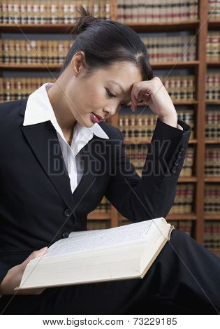 Asian woman reading library reference book
