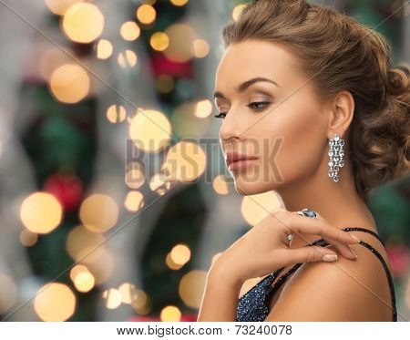 people, holidays and glamour concept - beautiful woman in evening dress wearing ring and earrings over christmas lights background