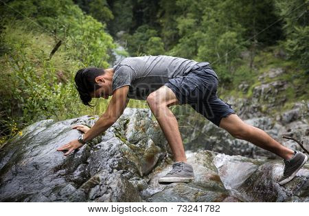 Man Clambering Over Rocky Terrain