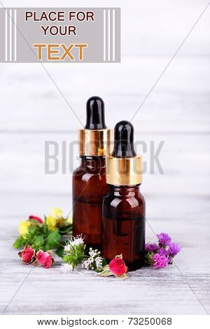 Essential oil with different medicine plants, on wooden background