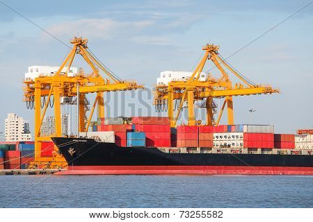 Cargo ship unloading container at port day time. poster