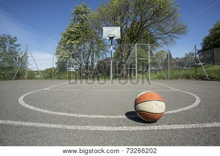 Used basketball on an outdoor court in daylight