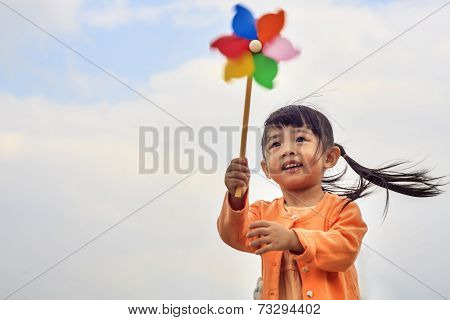 cute little girl on grass in summer day holds windmill for adv or others purpose use poster